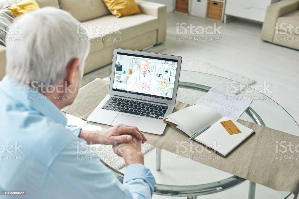 Zeitgenössische Rentner Beratung Arzt online vor Laptop zu Hause - Lizenzfrei Alter Erwachsener Stock-Foto