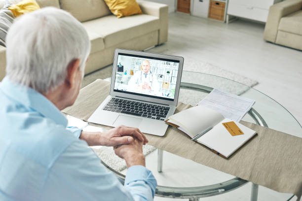 Contemporary pensioner consulting doctor online in front of laptop at home stock photo