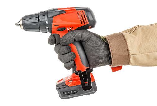 Contemporary red cordless drill in worker hand in black protective glove and brown uniform isolated on white background