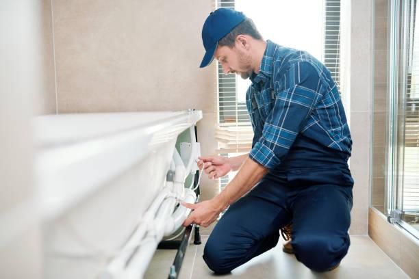 Técnico contemporáneo en ropa de trabajo instalando sistema de tuberías por bañera - foto de stock