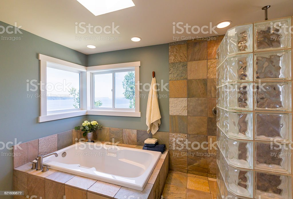 Contemporary upscale home spa bathroom interior with acrylic soaking tub stock photo