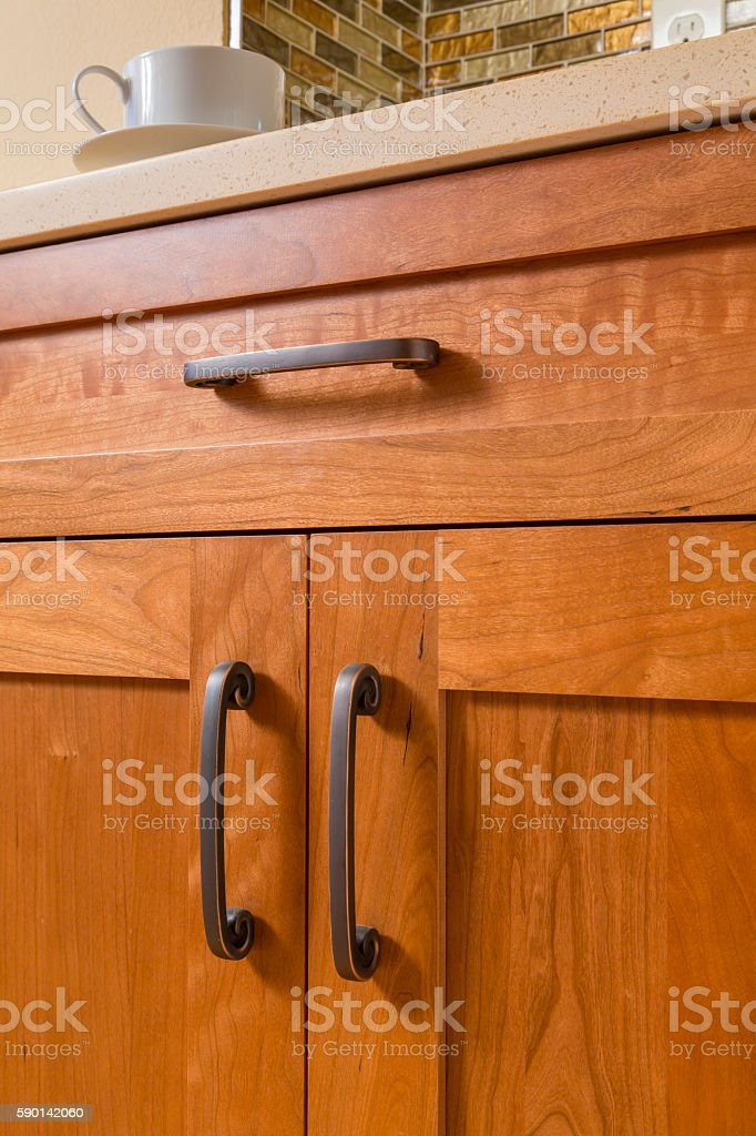 Contemporary upscale kitchen detail of high quality cherry wood cabinets stock photo