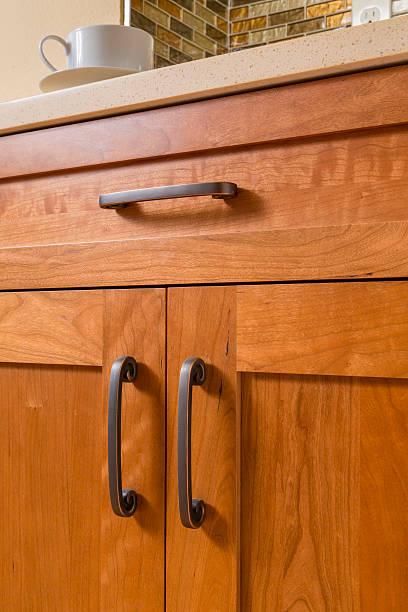 contemporary upscale kitchen detail of high quality cherry wood cabinets - griffe für küchenschränke stock-fotos und bilder