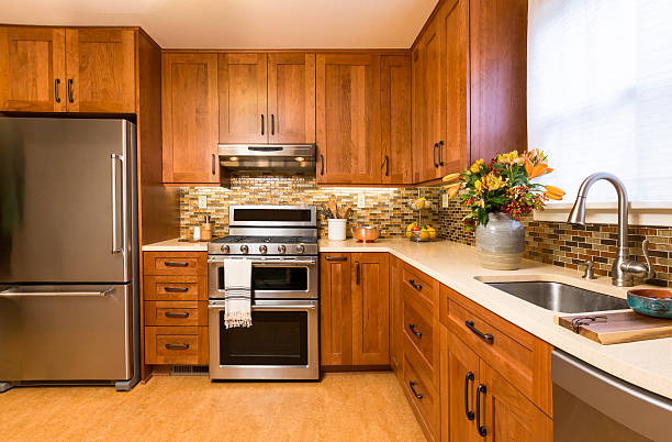 contemporary upscale kitchen with wood cabinets and stainless steel appliances - schrank stock-fotos und bilder