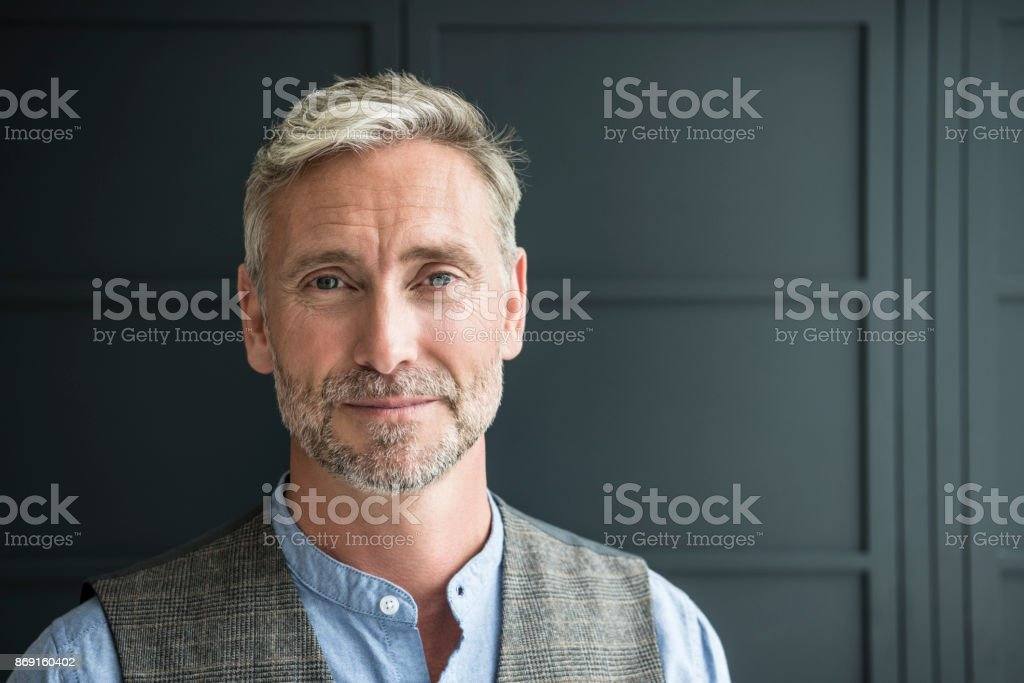 Contended mature man looking towards camera in waistcoat stock photo