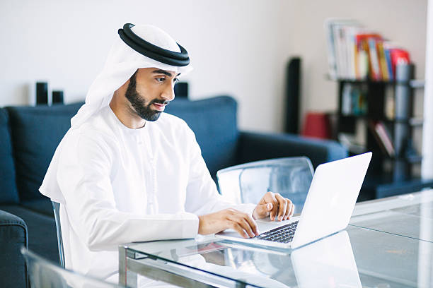 Content Arab Man Using Laptop at Home Arab man browsing social networks and doing business online using his laptop at home. Image contains some copy space. arabia stock pictures, royalty-free photos & images