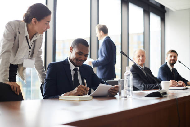 content attractive young business lady with badge standing at black colleagues and giving advices him with papers while he analyzing information during conference break - government stock pictures, royalty-free photos & images