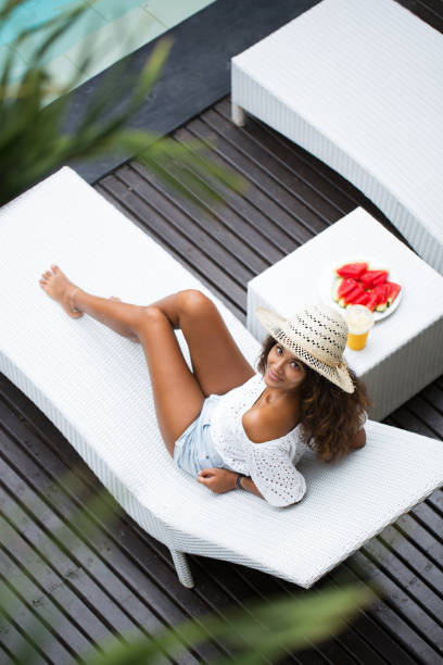 Content Beautiful Woman Resting on Chaise Longue stock photo