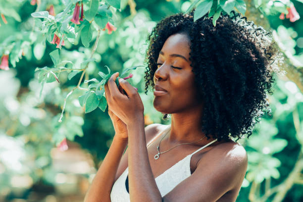 content black woman smelling flowers in park - scented stock photos and pictures