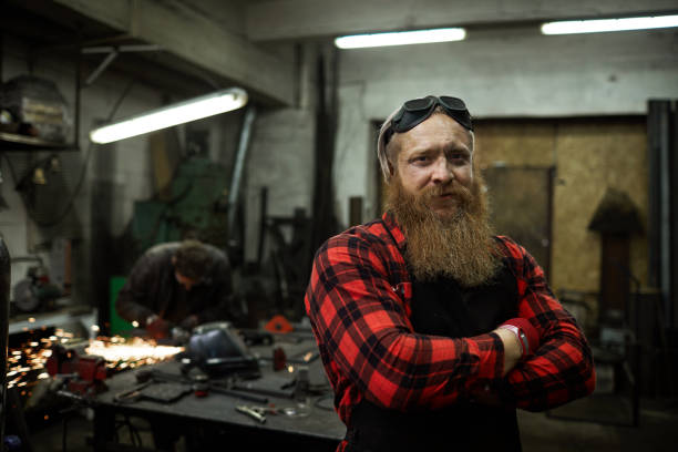 Content blacksmith in safety goggles on head in welding shop Content confident strong male blacksmith with long beard wearing safety goggles on head standing in welding shop and looking at camera metal worker stock pictures, royalty-free photos & images