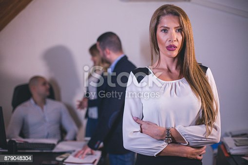 istock Content businesswoman posing while her colleagues are working in office 879048304