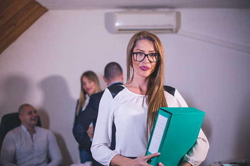 690855708 istock photo Content businesswoman posing while her colleagues are working in office 879048568