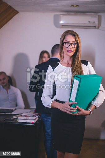 istock Content businesswoman posing while her colleagues are working in office 879048868