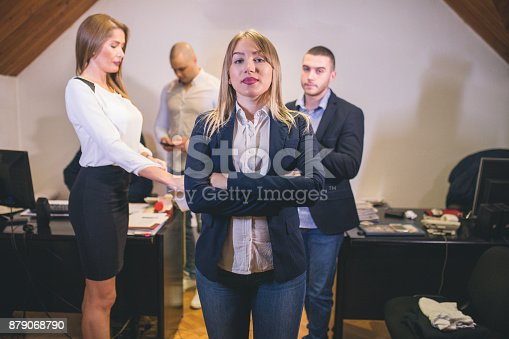 istock Content businesswoman posing while her colleagues are working in office 879068790