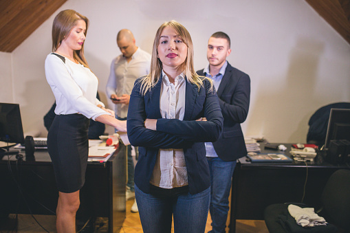 690855708 istock photo Content businesswoman posing while her colleagues are working in office 879068790