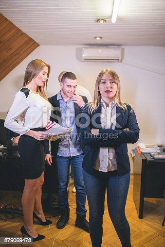 istock Content businesswoman posing while her colleagues are working in office 879069478