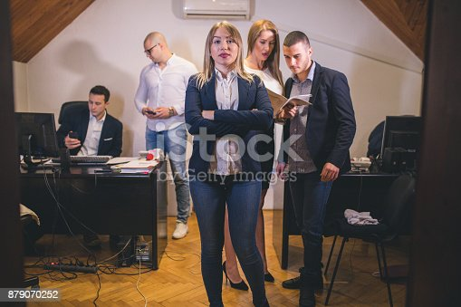 istock Content businesswoman posing while her colleagues are working in office 879070252