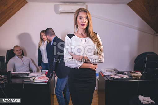 istock Content businesswoman posing while her colleagues are working in office 879070836