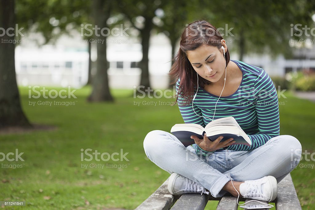 Content casual student sitting on bench reading stock photo
