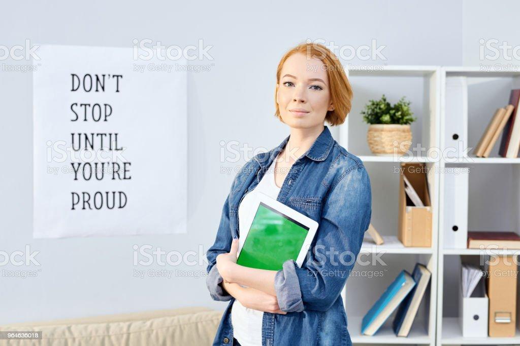 Conteúdo jovem ruiva proposital confiante na jaqueta jeans abraçando digital tablet e olhando para câmera no escritório moderno - foto de acervo