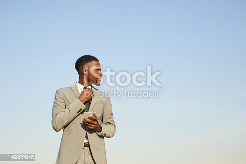 973213156istockphoto Content confident stylish young African-American businessman in beige suit standing against clear sky and adjusting necktie while using smartphone 1146022845
