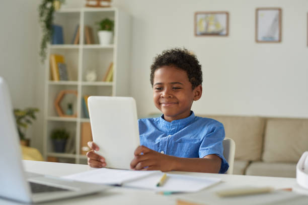Content cute Afro-American boy sitting at table in living room and using tablet while communicating via video conferencing app stock photo