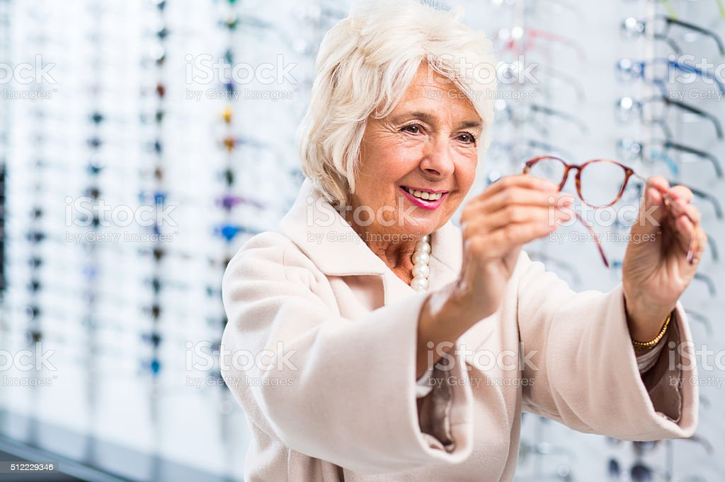 Content elderly lady buying eyeglasses stock photo