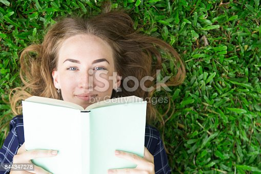 862602714 istock photo Content Girl Lying on Grass and Reading Book 844347278