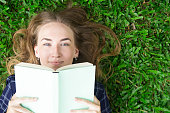 Content Girl Lying on Grass and Reading Book
