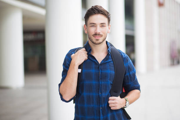 content handsome young man with backpack in city - adult student stock photos and pictures