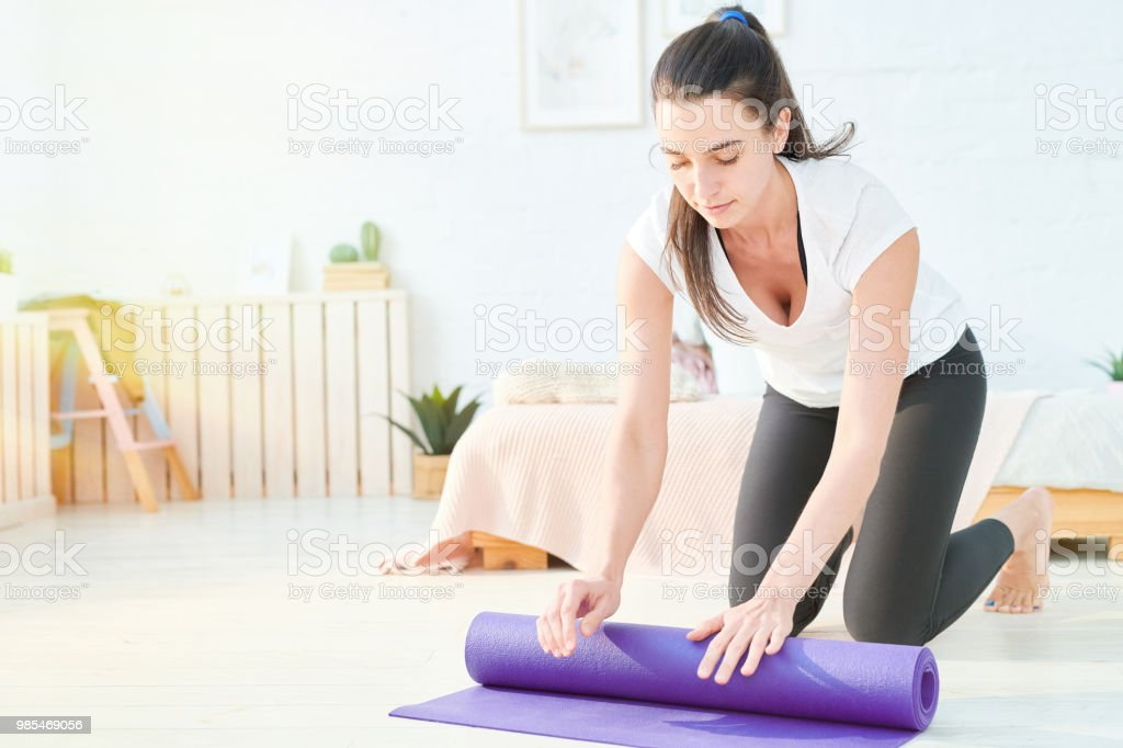Content healthy attractive young woman rolling yoga mat after practice at home stock photo