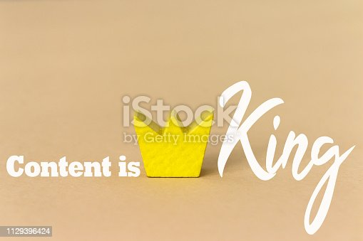 491520835 istock photo content is king, Business and Technology concept. Mobile phone on a wooden table and a gray background 1129396424