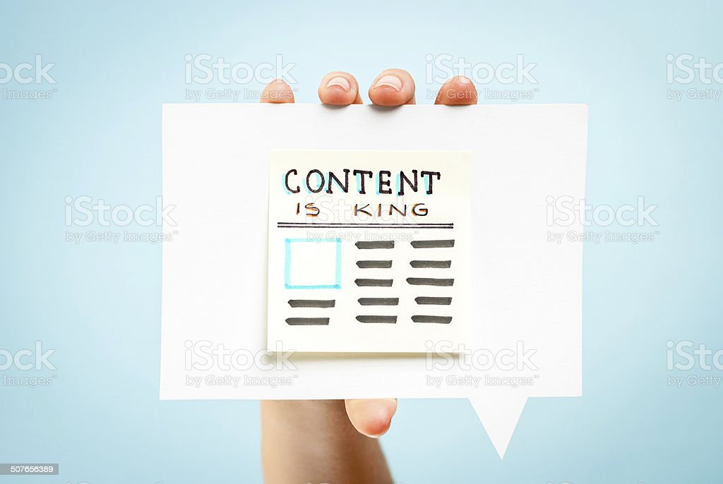 Content is king message newspaper hand blue background concept stock photo