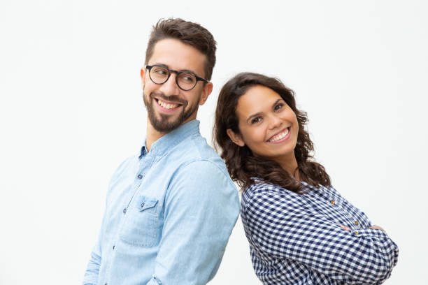 Content man and woman standing back to back stock photo