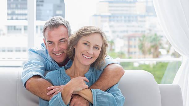 content man hugging his wife on the couch - ouder volwassenen koppel stockfoto's en -beelden