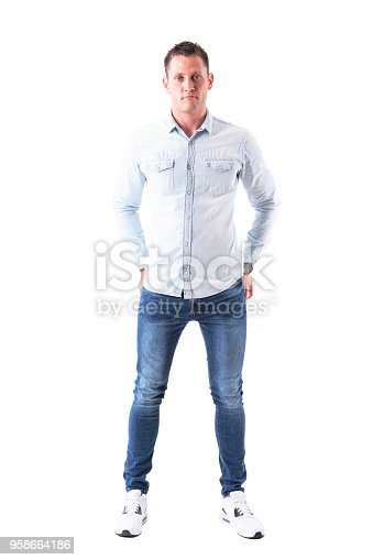931173966istockphoto Content man in light blue shirt and jeans looking at camera with hands in back pockets. 958664186