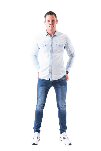 931173966 istock photo Content man in light blue shirt and jeans looking at camera with hands in back pockets. 958664186