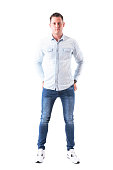 istock Content man in light blue shirt and jeans looking at camera with hands in back pockets. 958664186