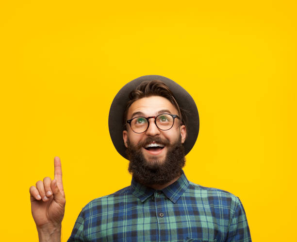 content man pointing up on orange - finger point stock photos and pictures