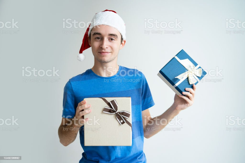 Content man wearing Santa Claus hat and showing gift boxes. Guy...