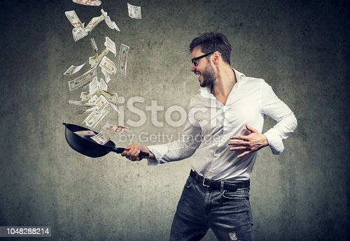 istock content man with frying pan full of dollar bills 1048288214
