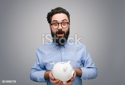 istock Content man with piggy bank on gray 924969728