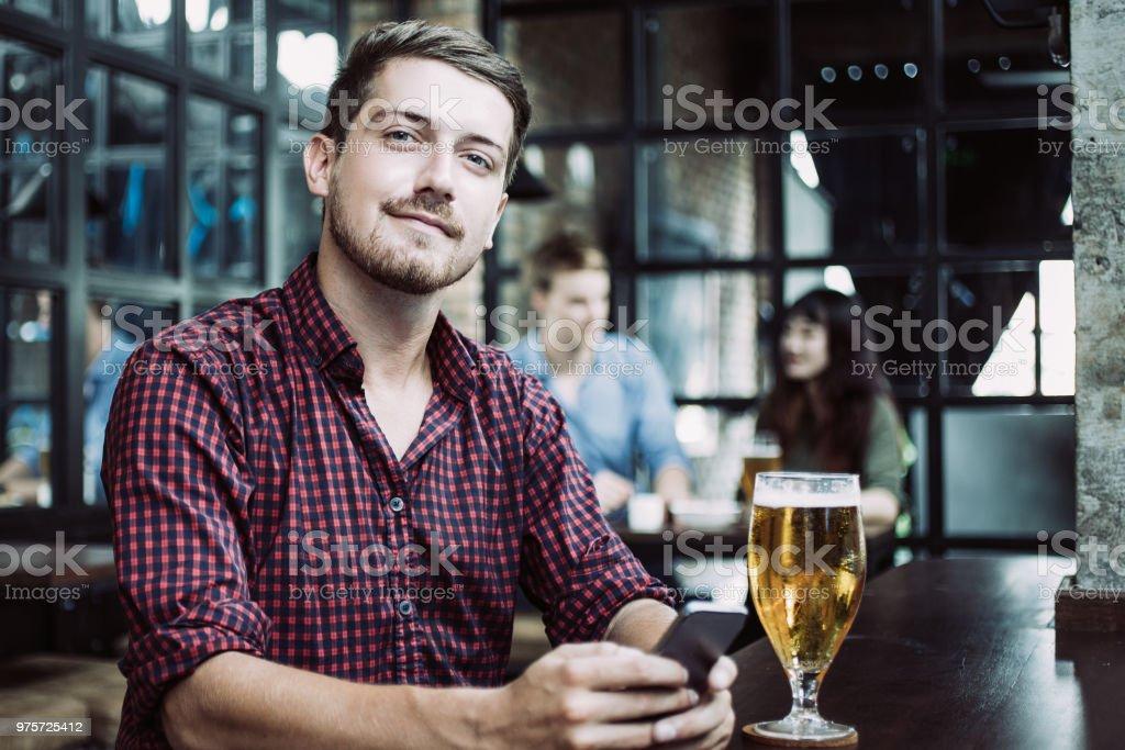 Content-Mann mit Smartphone und Bier im Pub - Lizenzfrei Arbeitsplatte Stock-Foto