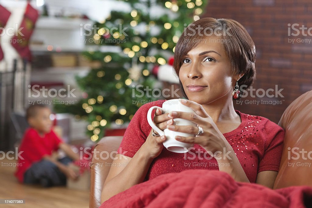 Content mom on Christmas morning, family opening gifts in background royalty-free stock photo
