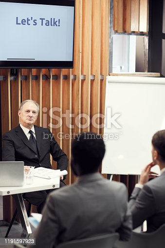 1069233370 istock photo Content pensive senior business speaker with gray hair sitting in conference room and listening to audience during discussion of presentation 1191597923