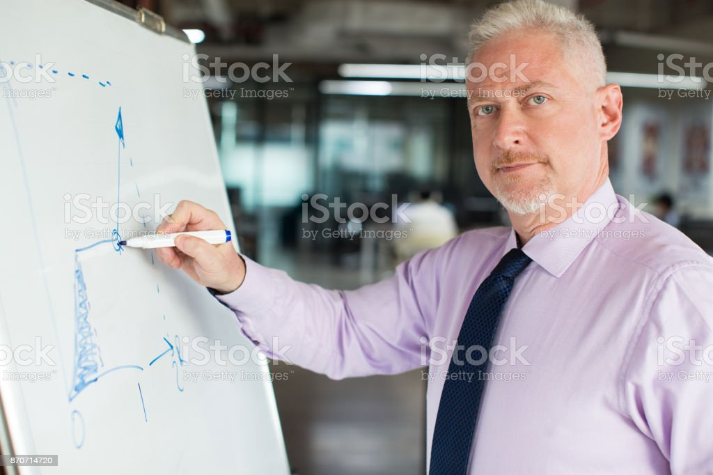 Content Senior Expert Drawing Line Chart stock photo