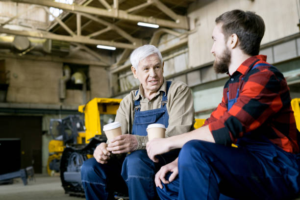 Content senior factory worker in overalls talking to young employee and sharing experiences during coffee break at industrial plant stock photo