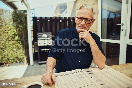 116379055 istock photo Content senior man reading a newspaper at his patio table 961404914