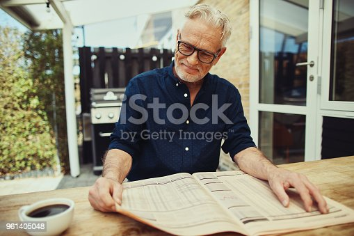 116379055 istock photo Content senior man reading a newspaper at his patio table 961405048