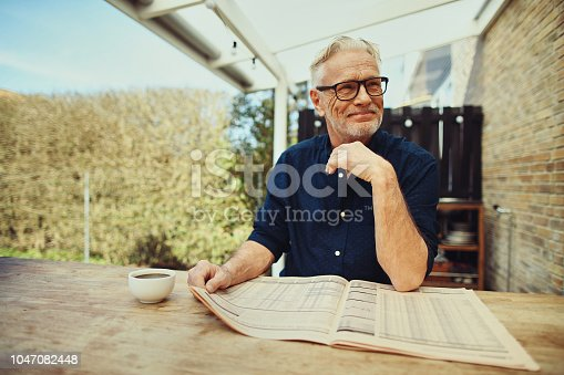 116379055 istock photo Content senior man reading the newspaper on his patio 1047082448